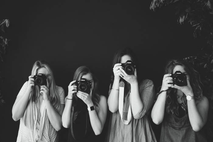A black and white photo of four beginners photographers holding DSLR cameras
