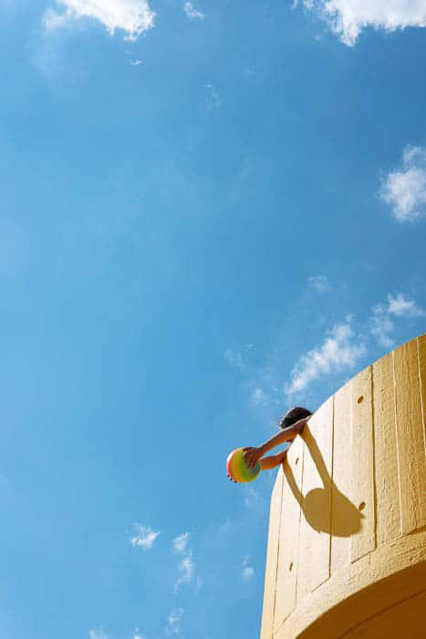 A bright and airy photo of a child playing in a tower against a blue sky, demonstrating the rule of thirds in beginner photographer