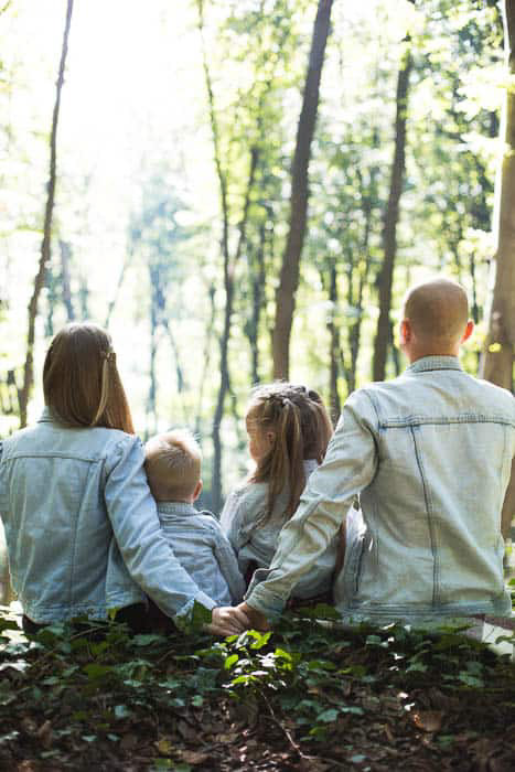 A bright and airy photo of a family sitting in the woods