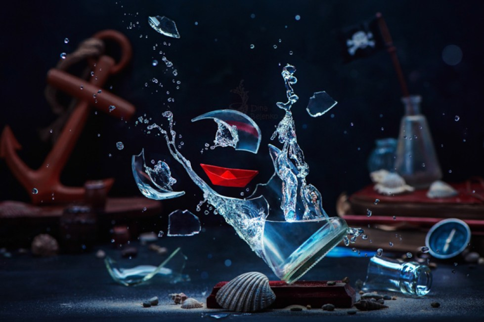 Still life of a glass of water breaking surrounded by sea themed objects
