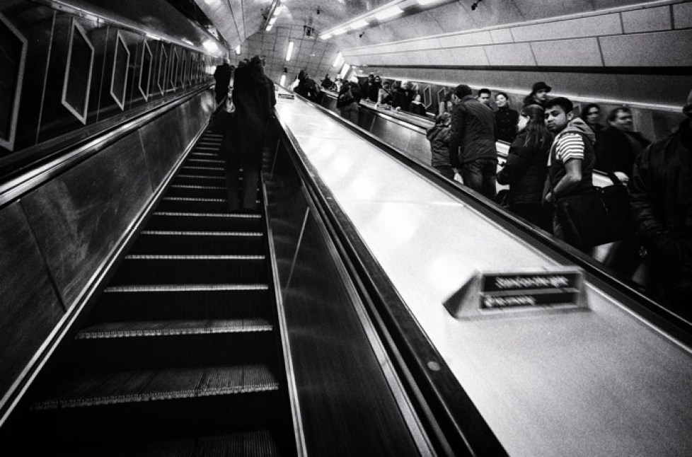 Black and white image of people on a metro station elevator