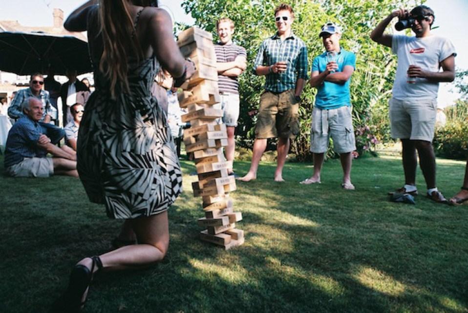 Candid photo of people playing giant jenga outdoors