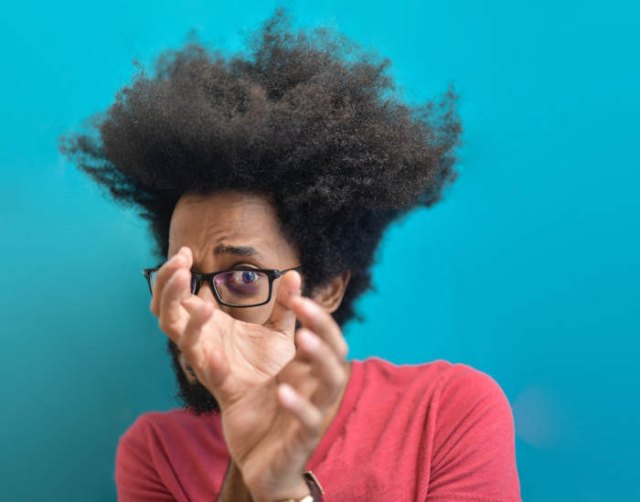 portrait of a young black man with glasses looking through his hands