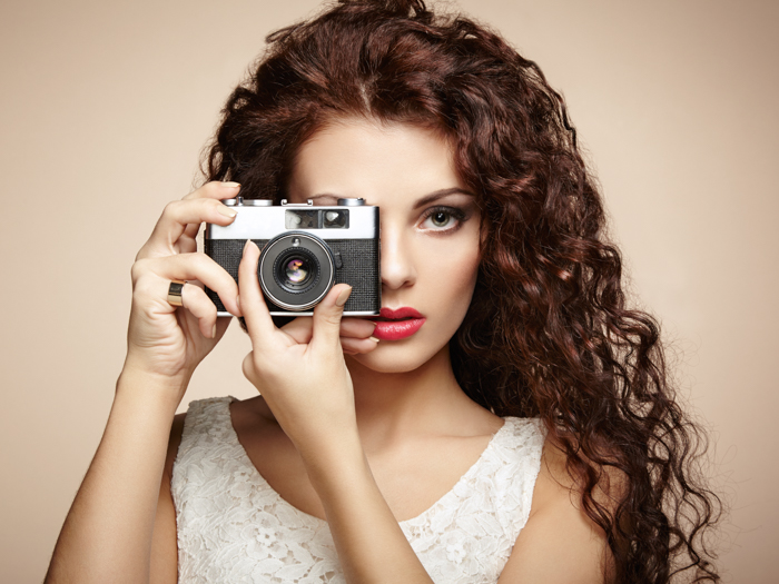 photo of a woman holding a camera over one eye