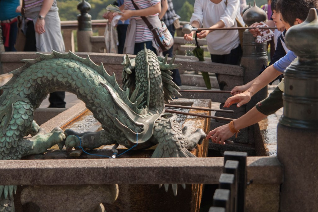 People washing their hands in a dragon fountain