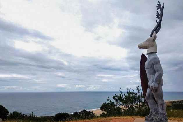 Escultura de surfista com cabeça de veado na Nazaré