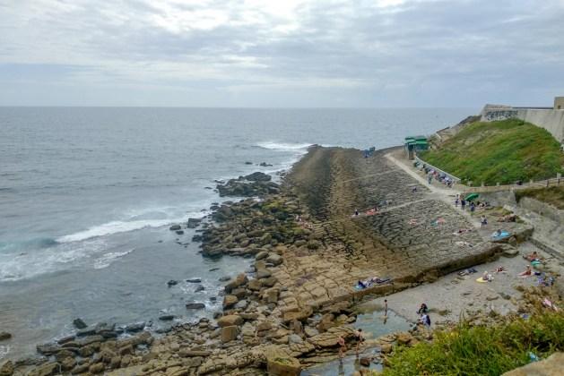Vista sobre as pedras ricas em iodo da Praia da Consolação onde de avista o restaurante Sol é Vida
