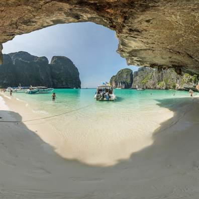 These overhanging rocks and their shadow make a perfect frame for the famous Maya Bay beach in Thailand.