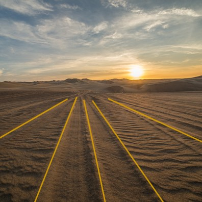 Huacachina Desert, Peru. The tyre marks on the sand lead the eye to the magnificent distant sand dunes and the sunset.