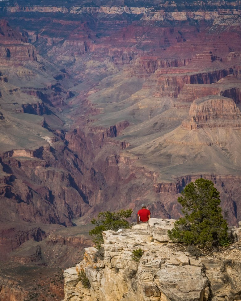 Man sitting on a rock above the Grand Canyon
