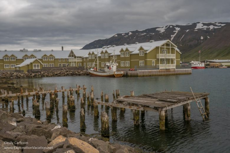 Old rotting pilings with and traditional-looking hotel in the background