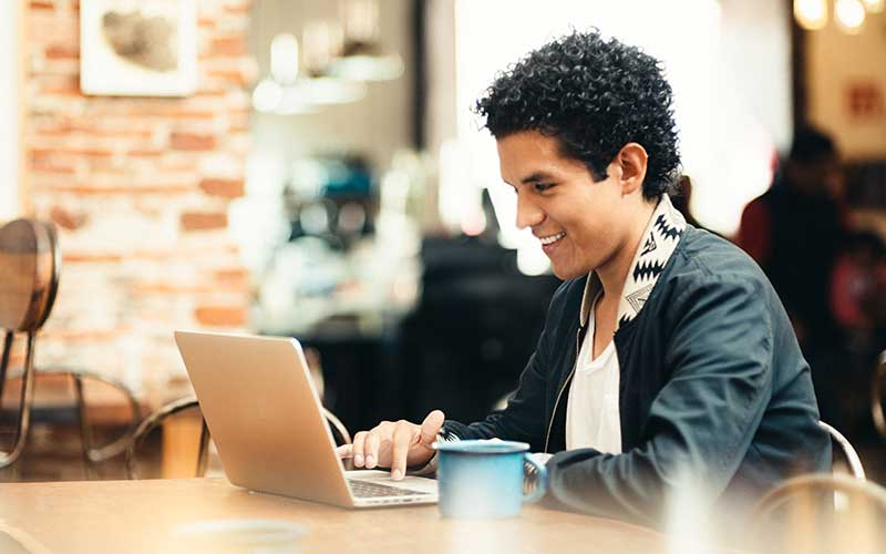 image of youth in a coffee shop with computer accessing online learning