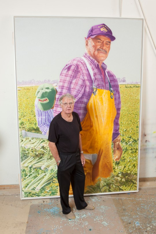 "Don Coen with his 9-foot-high acrylic on canvas ""Angel"" from ""The Migrant Series"" at the Phoenix Art Museum. Image courtesy of the artist."