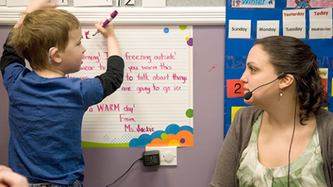 Teacher and child using sound amplification device