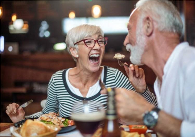 retired couple eating dinner on main street