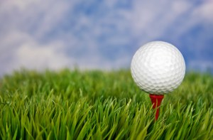 close up of golf ball on red tee in grass