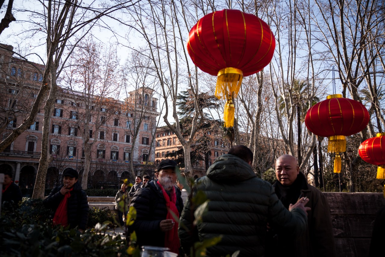Men take a cigarette break during Chinese New Year celebrations in Piazza Vittorio.