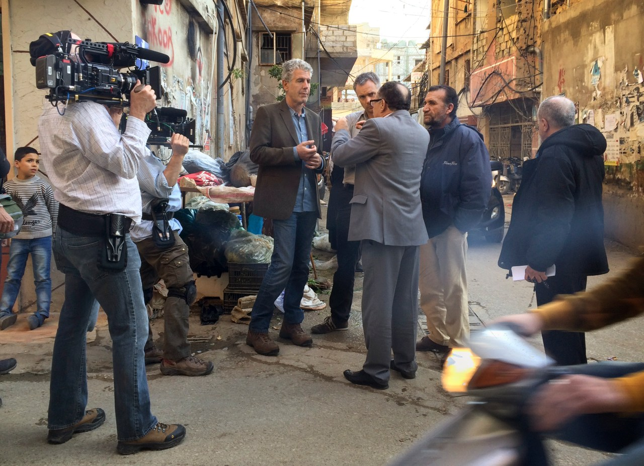 Bourdain and Nick Patton Walsh (to Bourdain's immediate left) speak with Mr. Najem (back to camera).