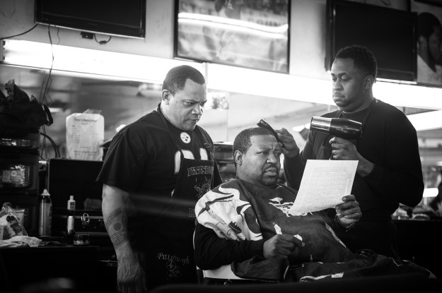 """1. Reggie """"Feeny"""" Ward Jr. reads a football poll to barbers Kevin Adams and Edward Azeem. Feeny was a regular customer until he passed away a few months ago. / 2. Joseph Cook waits for a ride outside of Dave's Barber Shop after getting his hair cut."""