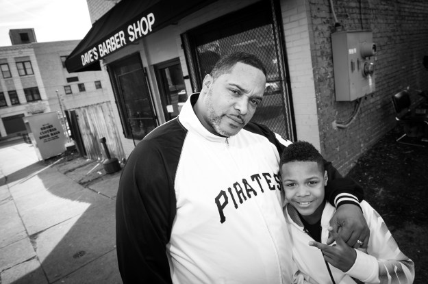 1. Richard Smith poses with his son Noah outside of Dave's Barber Shop after they both received fresh haircuts. Smith, a regular, has been bringing his son since his first haircut. / 2. Ericka Bibins smiles as her son tries to hide when the barber jokes about his upcoming haircut.
