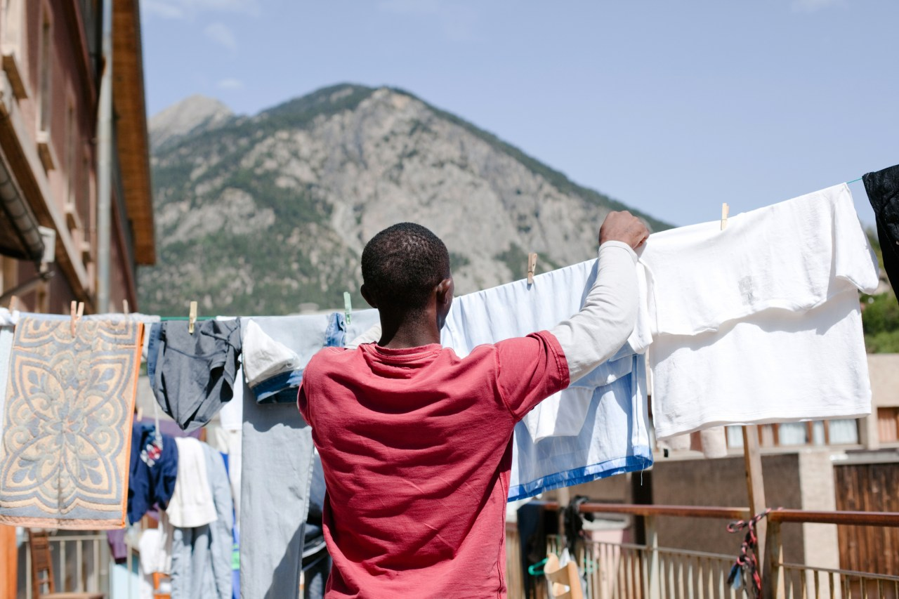 A migrant from Guinea hangs clothes out to dry on the terrace of the emergency shelter in Briançon.
