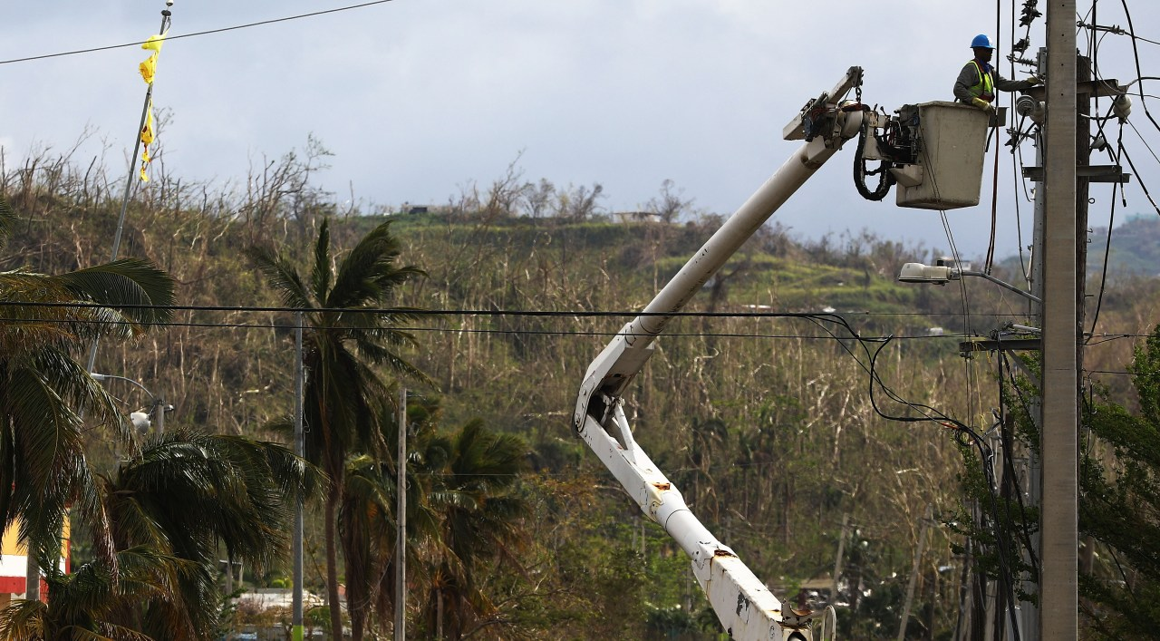 A worker repairs power lines in San Isidro, Puerto Rico on Oct. 5, about two weeks after Hurricane Maria devastated the island. (Photo by Mario Tama via Getty Images)