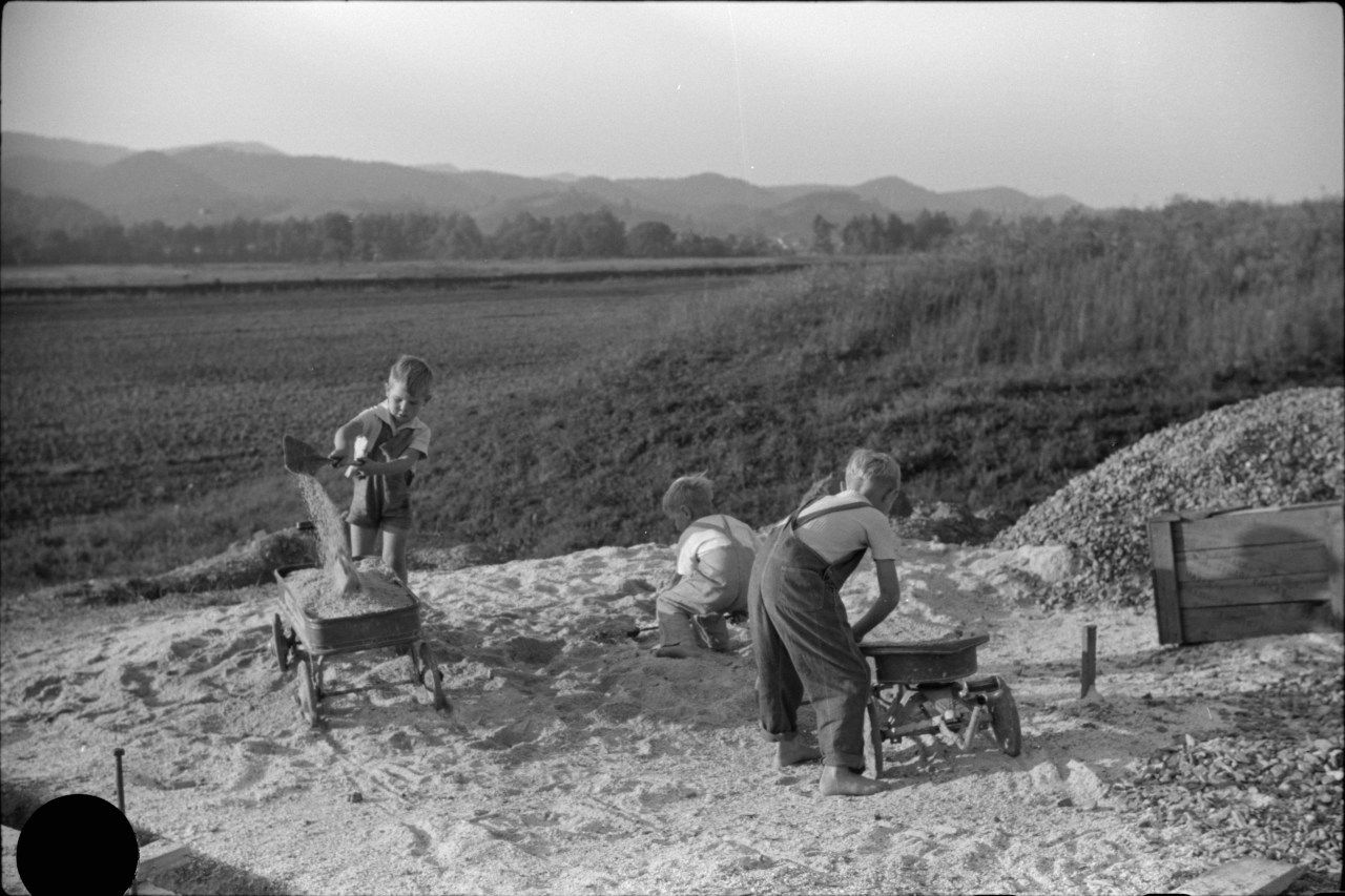 Children play with sand in Tygart Valley, September 1938. The large black circle at the lower left of this frame was made by a hole punch, the preferred method of the photo editor to reject frames he did not wish to distribute. Photo by Marion Post Wolcott.