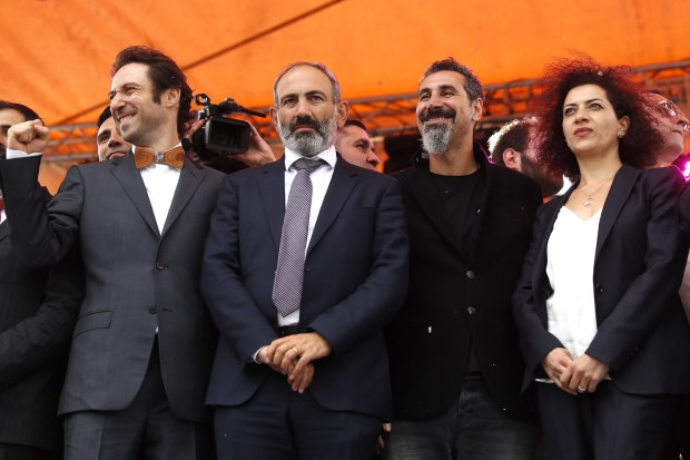 Pashinyan (second left), singer Serj Tankian (second right), and Pashinyan's wife Anna Akopyan (right) celebrate Pashinyan's election. Photo by Artyom Geodakyan/TASS via Getty Images.