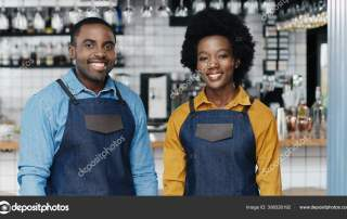 Portrait of young African American cheerful couple of bartenders in aprons smiling to camera happily. Happy waiter and waitress posing in cafe. Joyful man and woman, barristas at work. Job in service.