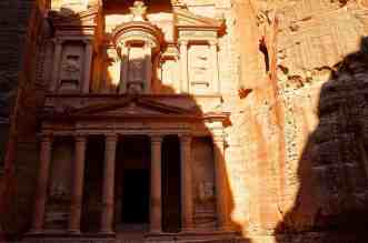 Walking into the ancient city of Petra in Jordan - A large stone building with Petra in the background - Wadi Rum