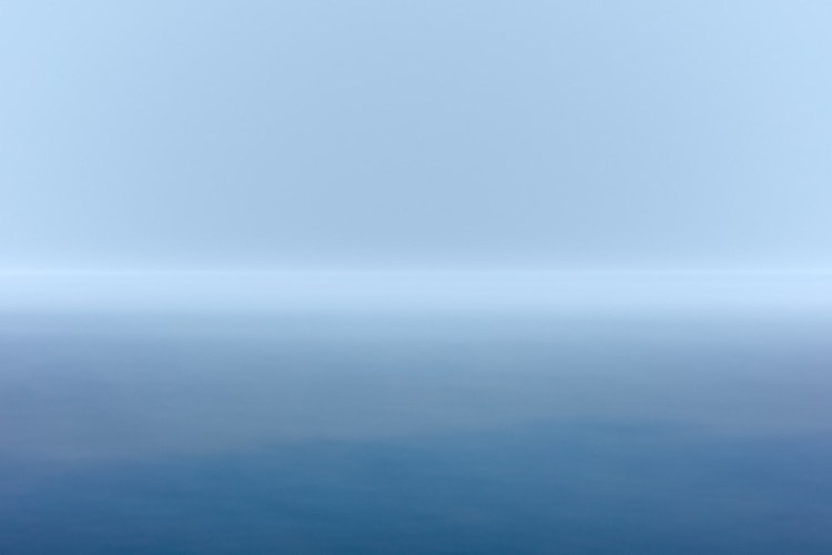 Blue landscape and horizon seen through thin clouds