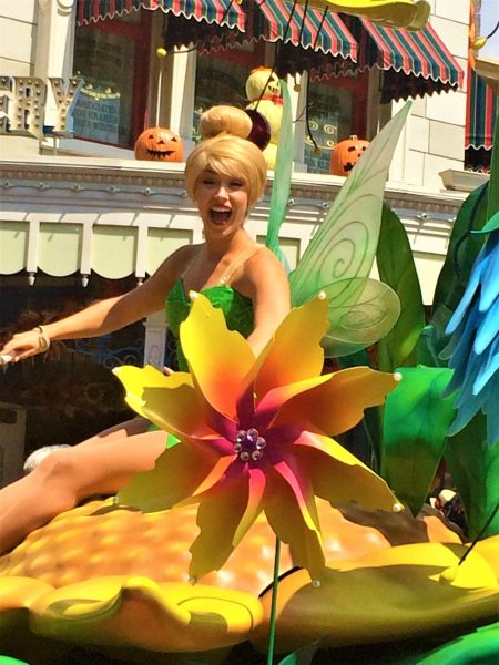Tinker Bell sitting on top of her float during a parade at Walt Disney World
