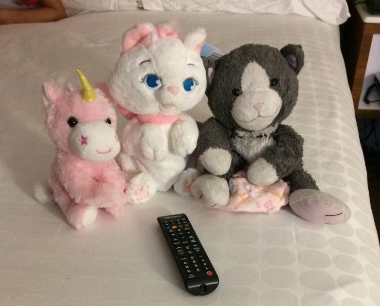 Mousekeeping arranging children's toys on the bed at Disney's Pop Century