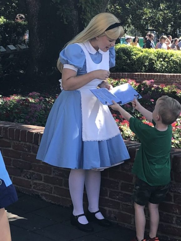 Child giving Alice an autograph book to sign
