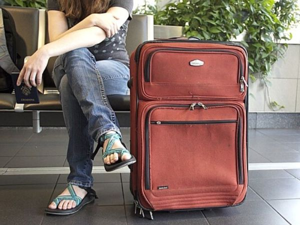 A lady sitting next to a large Suitcase