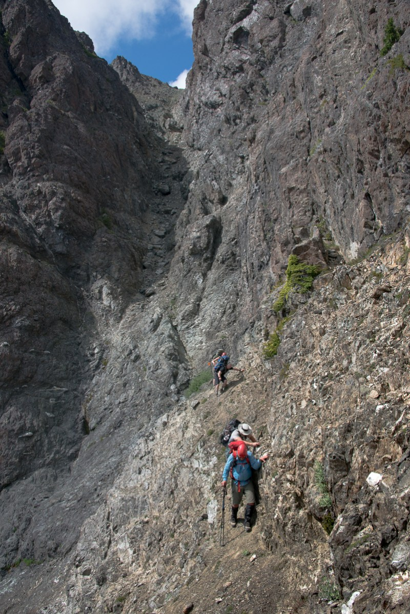 crossing the gravely ledge after descending the steep choss-filled gully.