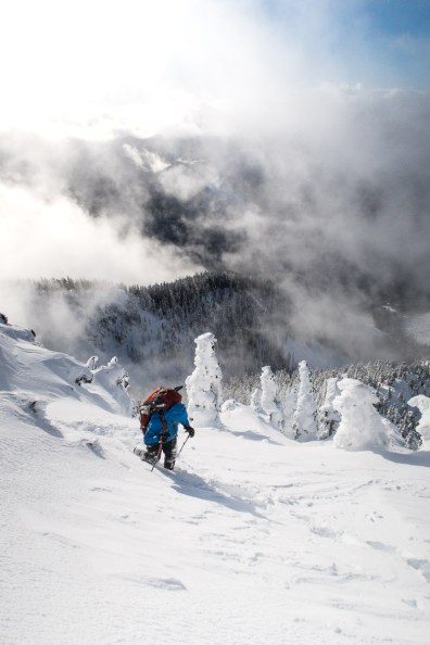 a figure hikes up a very steep snowslope, a river valley falls away in the background