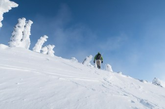 a person hiking up a snowy mountain on Vancouver Island
