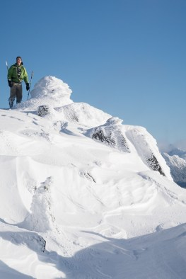a lone figure raises his arms in celebration after snowshoeing or hiking to the top of Mount Elliot on Vancouver ISland