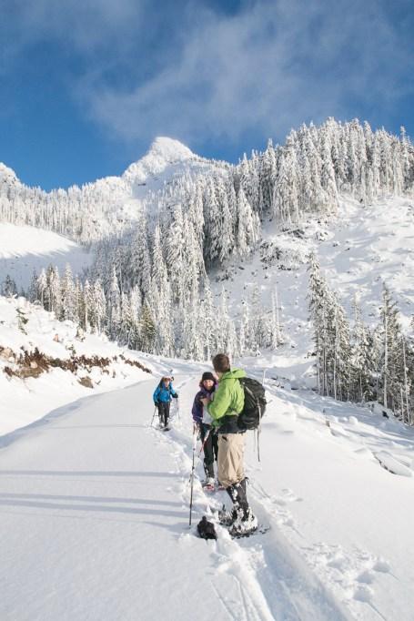 three figures descending a mountain, mount Elliot, on snowshoes