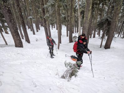 a man carries a child on his shoulders and hauls a sled up a snowslope wearing snowshoes