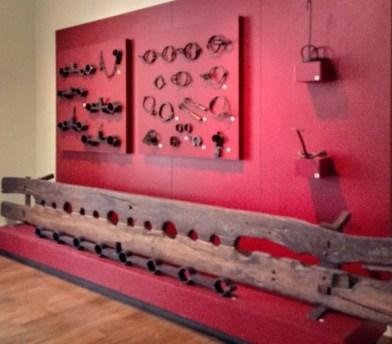 """... núcleo dos instrumentos de tortura que remetem à violência da escravidão. Junto ao núcleo a televisão com a projeção da obra """"Justiça e Barbárie"""" de Jaime Lauriano."""