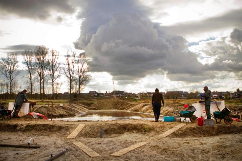 Archeologen aan het werk aan de zeefput. Dit reservoir werd machinaal uitgegraven om het gebruikte zeefwater te recycleren: het water wordt in de put opgevangen en door middel van pompen (waarop heel fijne zeven zitten) opnieuw als spoelwater gebruikt. Op de achtergrond daalt het terrein af richting Schelde.