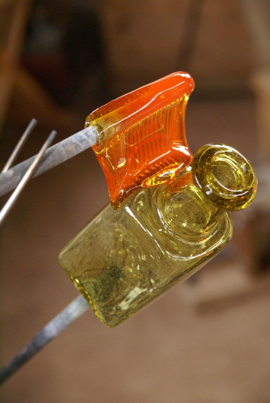 Normaal is geblazen glas is altijd bolvormig. Maar door glas te blazen in een moule worden kubusvormige objecten gemaakt of glas met een reliëf. Sommige onderdelen worden niet geblazen maar 'geplakt', zoals een oortje aan deze fles.