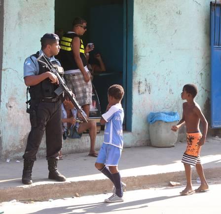Crianças observam o PM armado