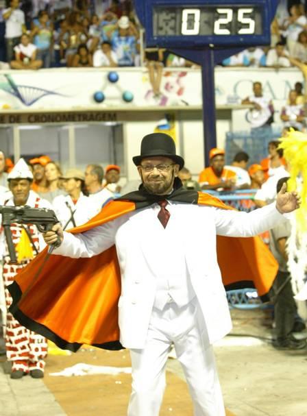 José Wilker com a capa preta e a metralhadora 'Lurdinha', representando o político Tenório Cavalcanti, no desfile da Grande Rio, em 2007