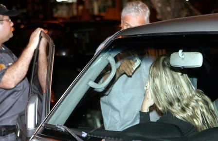 Amanda chega à delegacia no banco do carona de seu Pajero, que está com licenciamento vencido e o vidro trincado
