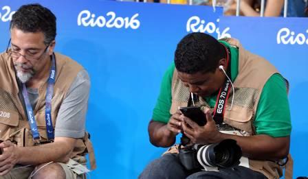 João Maia trabalhando no Rio2016 sentado de costas para um painel azul olhando no visor da câmera profissional com uma lente fixa de 300 mm da série branca da Canon e um Smartphone com fone de ouvido . João usa camiseta verde e colete de imprensa marrom. Ao lado um senhor com camiseta cinza e colete de imprensa marrom.