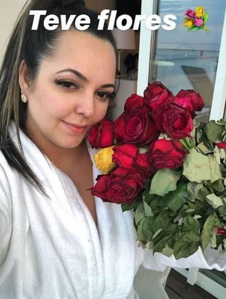 Priscila mostra as flores que Ronaldinho deu a ela