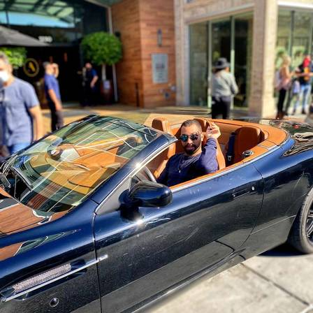 Gil do Vigor poses in a luxury car